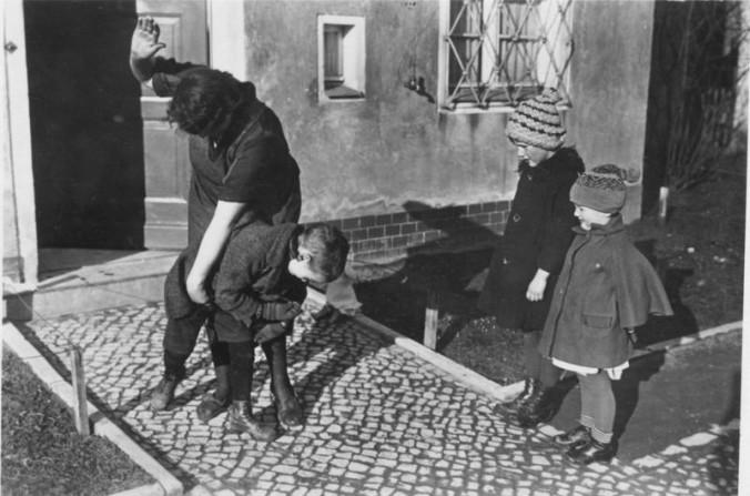 """Scherl Bilderdienst: Kindererziehung [um 1935] """"Fachleute"""" schauen der handgreiflichen Erziehungsmethode bei ihrem Spielgefährten zu. Ob sie danach an der Reihe sind?"""